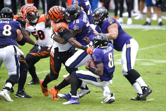 Cincinnati Bengals defensive end Carlos Dunlap (96) is able to sack Baltimore Ravens quarterback Lamar Jackson (8) in spite of being blocked by Ravens offensive tackle Orlando Brown (78) during the first half of an NFL football game, Sunday, Oct. 11, 2020, in Baltimore. (AP Photo/Nick Wass)