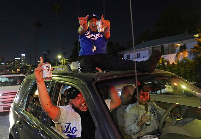 Los Angeles Dodgers fans celebrate on Sunset Blvd. after watching the broadcast of Game 6 of the baseball World Series in Los Angeles on Tuesday, Oct. 27, 2020. The Los Angeles Dodgers defeated the Tampa Bay Rays 3-1 and won the World Series. (AP Photo/Damian Dovarganes)
