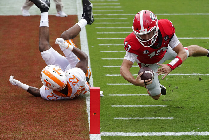 Georgia quarterback Stetson Bennett (13) dives past Tennessee defensive back Jaylen McCollough (22) to score a touchdown in the first half of an NCAA college football game Saturday, Oct. 10, 2020, in Athens, Ga. (AP Photo/John Bazemore)