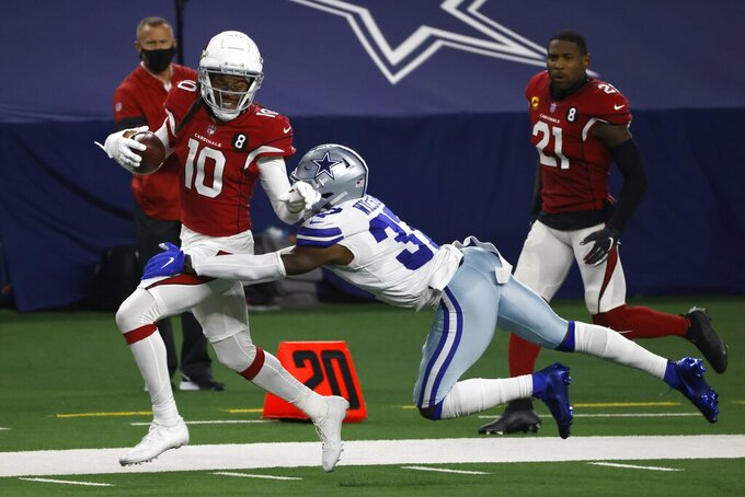 Arizona Cardinals wide receiver DeAndre Hopkins (10) is brought down after a long gain on a catch by Dallas Cowboys' Donovan Wilson (37) in the second half of an NFL football game in Arlington, Texas, Monday, Oct. 19, 2020. (AP Photo/Ron Jenkins)