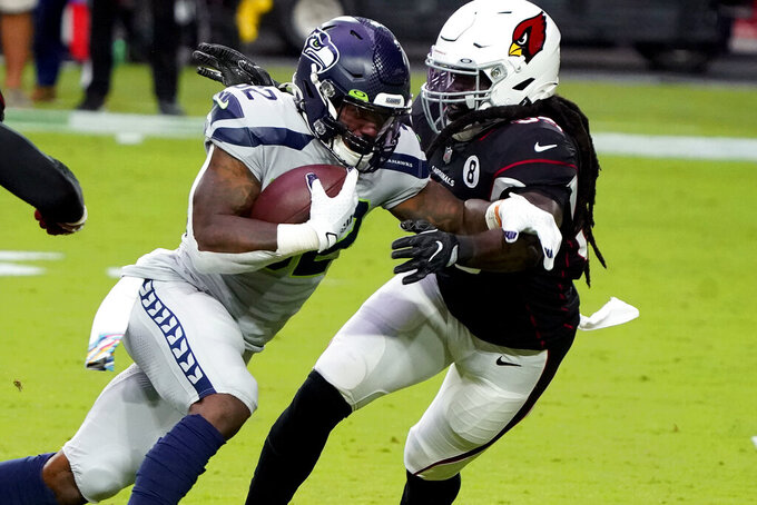 Seattle Seahawks running back Chris Carson (32) runs as Arizona Cardinals outside linebacker De'Vondre Campbell defends during the first half of an NFL football game, Sunday, Oct. 25, 2020, in Glendale, Ariz. (AP Photo/Rick Scuteri)