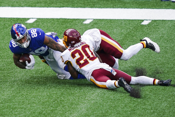 Washington Football Team's Temarrick Hemingway (88) is tackled by Washington Football Team's Jimmy Moreland (20) during the first half of an NFL football game Sunday, Oct. 18, 2020, in East Rutherford, N.J. (AP Photo/John Minchillo)