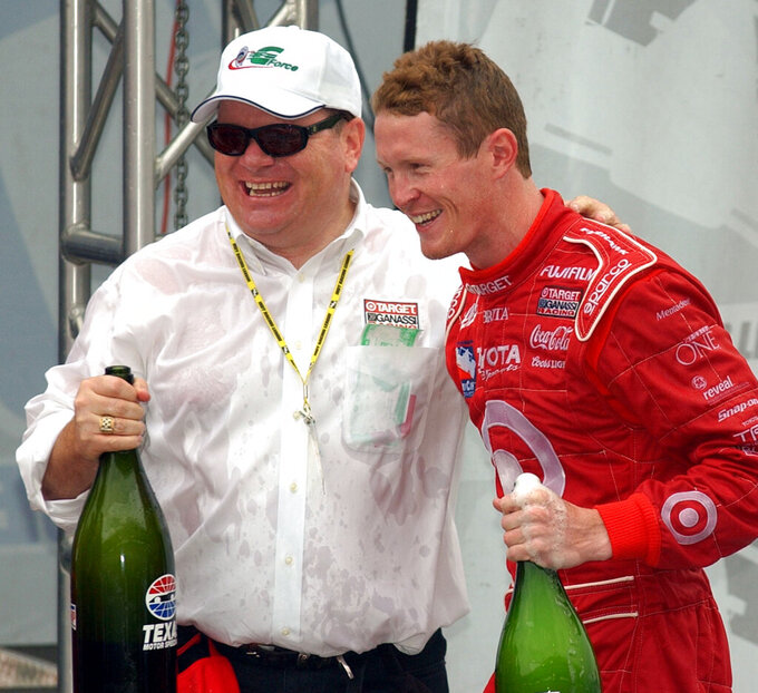 FILE - In this Sunday, Oct. 12, 2003, file photo, team owner Chip Ganassi, left, and 2003 IRL champion Scott Dixon, right, celebrate following the IRL Chevy 500 race at Texas Motor Speedway in Fort Worth, Texas. Ganassi knew Dixon as a quiet kid in a paddock full of superstars when he hired him four races into the 2002 season.  (AP Photo/Tony Gutierrez, File)