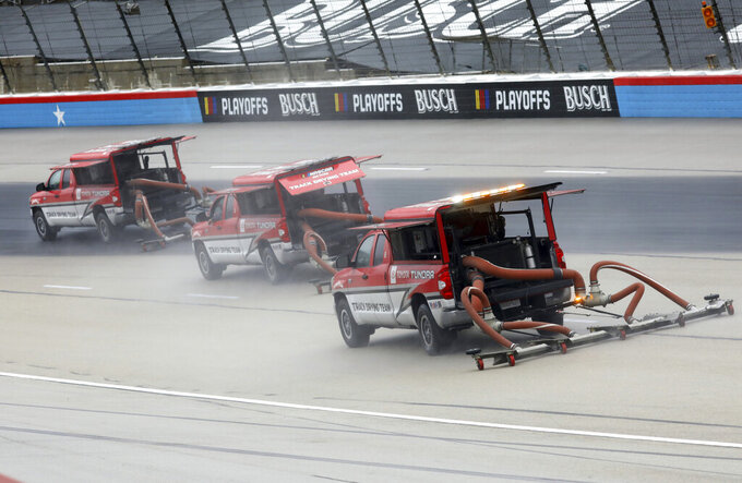 Drying trucks continue to prepare the track for a possible NASCAR Cup Series auto race at Texas Motor Speedway in Fort Worth, Texas, Tuesday, Oct. 27, 2020. The race was stopped on Sunday because of drizzle and misty conditions that allowed drivers to complete just 52 of 334 laps. Another 115 laps have to be completed to get to the halfway mark of 167 laps that would make Texas an official race. (AP Photo/Richard W. Rodriguez)
