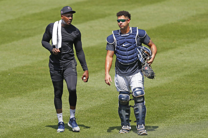 New York Yankees relief pitcher Aroldis Chapman, left, leaves the field after a bullpen session with catcher Gary Sanchez after a bullpen session during a baseball summer training camp workout Sunday, July 5, 2020, at Yankee Stadium in New York. (AP Photo/Kathy Willens)