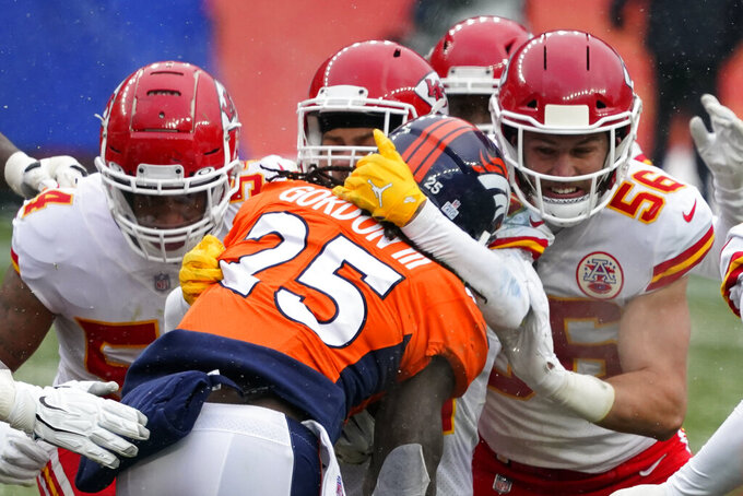 Denver Broncos running back Melvin Gordon (25) is brought down by Kansas City Chiefs linebacker Ben Niemann (56) and others during the first half of an NFL football game Sunday, Oct. 25, 2020, in Denver. (AP Photo/Jack Dempsey)