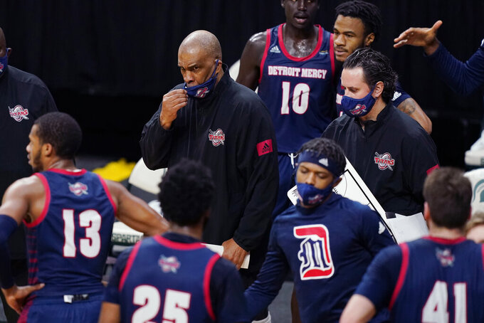 FILE- In a Dec. 4, 2020 file photo, Detroit Mercy head coach Mike Davis prepares to talk to his team during the first half of an NCAA college basketball game against Michigan State, in East Lansing, Mich. In a college basketball season unlike any other, players have had to adjust to coronavirus protocols and just general anxiety about what's to come. Even for those who manage to avoid catching the virus, the mental strain can be a real issue. Detroit Mercy's men's basketball program paused activities earlier this season, citing the mental health of its players. (AP Photo/Carlos Osorio, File)